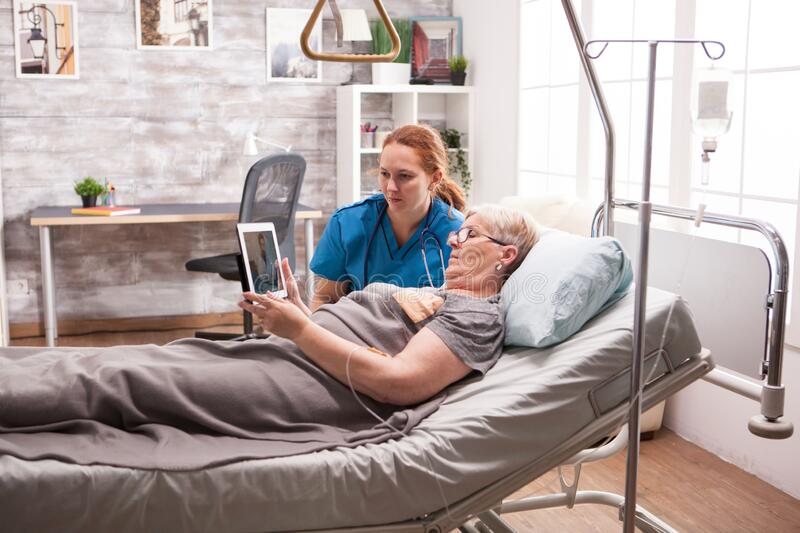 Female assistant in nursing home helping old female royalty free stock image