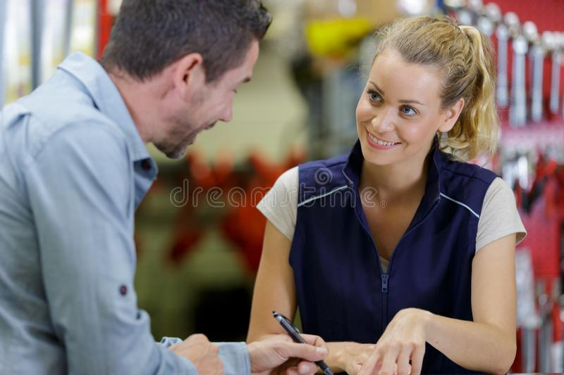 Female assistant serving customer in hardware store royalty free stock image