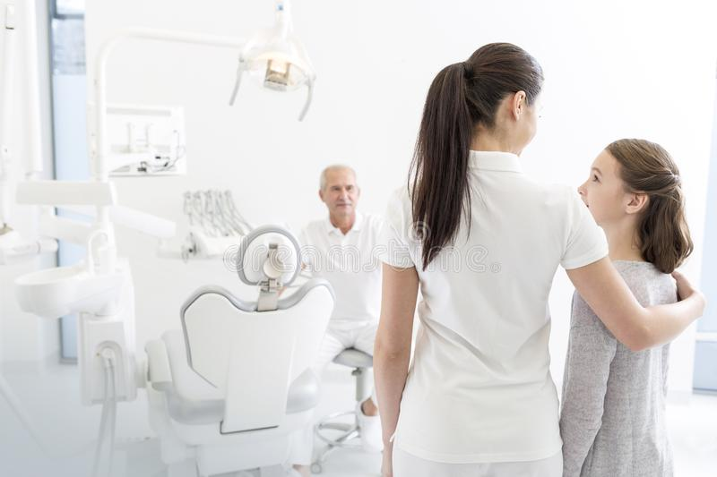 Female assistant talking to girl patient in front of dentist at clinic royalty free stock image