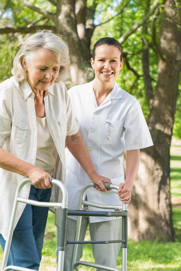 Female assisting mature woman with walker at park royalty free stock photo