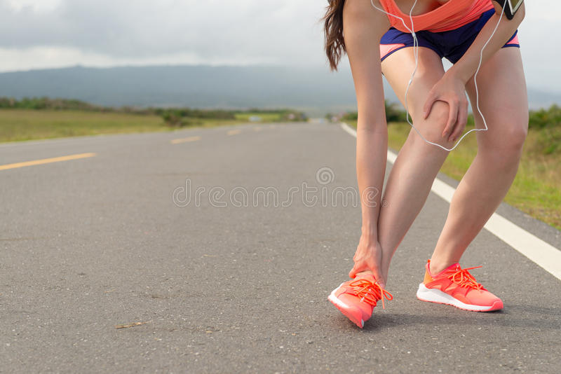 Female athlete ankle injury when running on road stock photos