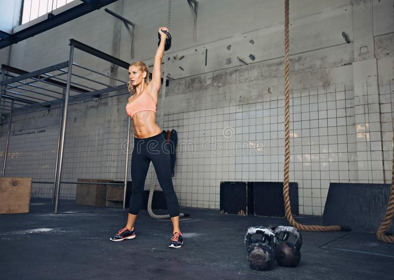 Female athlete in a crossfit workout. Young fitness woman lifting a heavy weight kettle bell at gym. Caucasian female athlete working out at gym. Fit young lady stock image