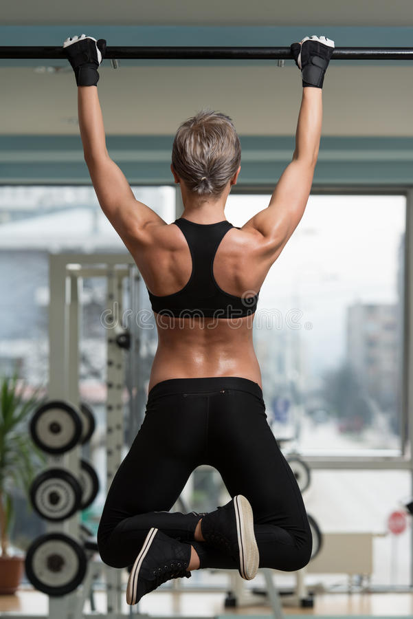 Female Athlete Doing Pull Ups. Chin-Ups In The Gym royalty free stock photos