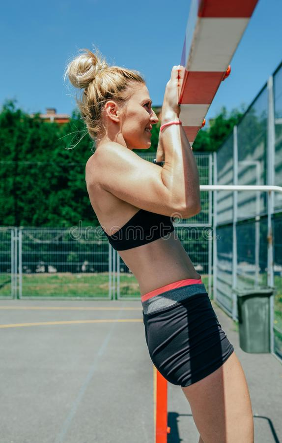 Female athlete doing pull-ups in a goal. Young female athlete doing pull-ups in a goal on a sports court royalty free stock images