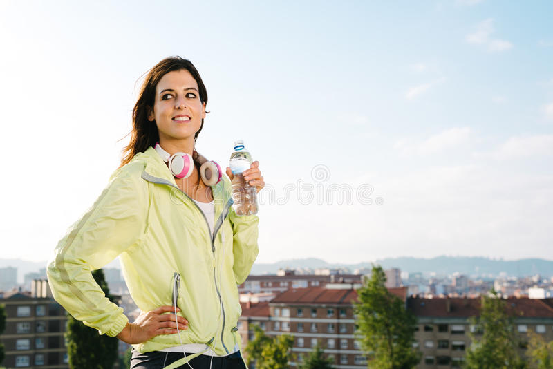 Female athlete drinking water on exercising break stock photography