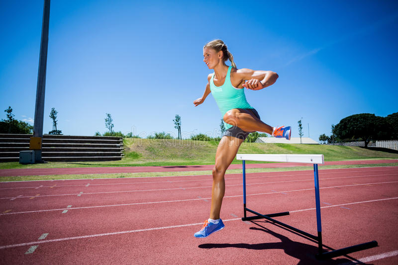 Female athlete jumping above the hurdle stock images