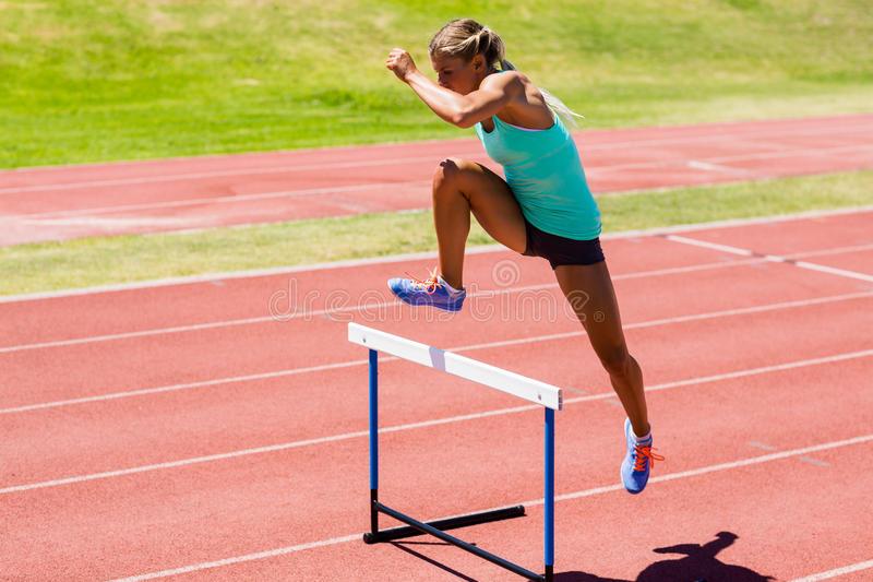 Female athlete jumping above the hurdle stock photos