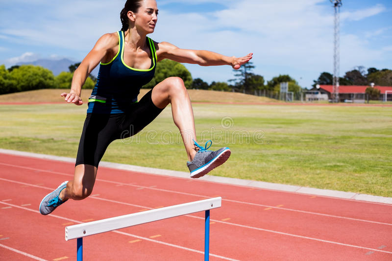 Female athlete jumping above the hurdle royalty free stock image