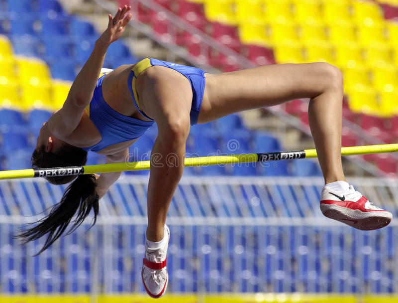 Female athlete is jumping pole vault during a sport competition stock images