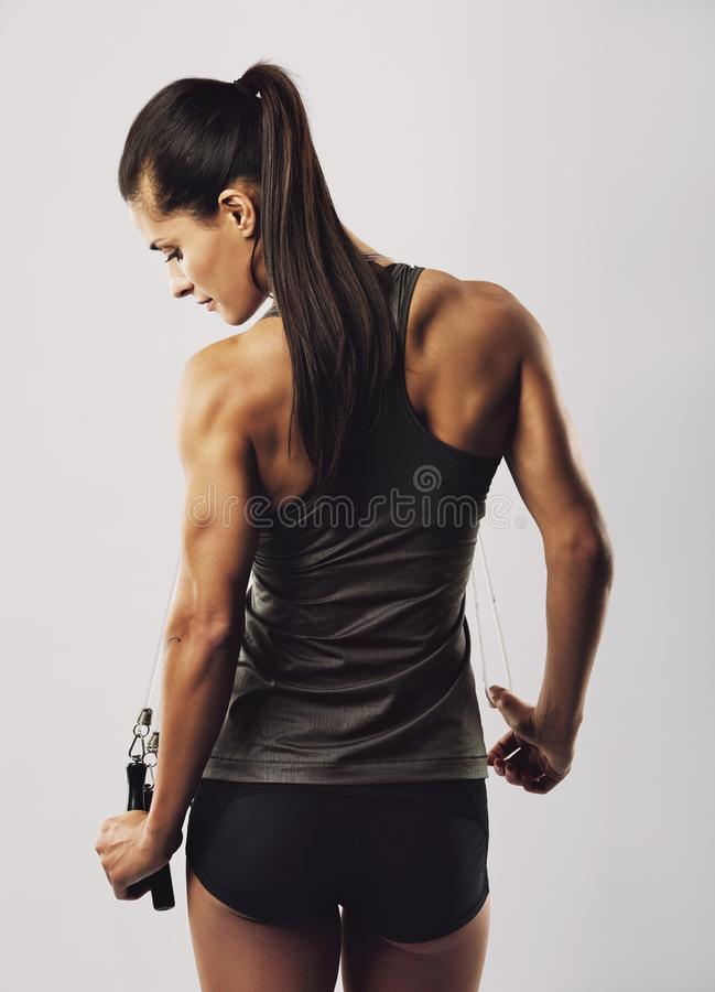 Female athlete with jumping rope posing on grey background stock images
