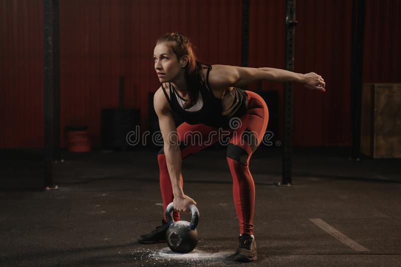 Female athlete lifting heavy weights. Sports woman holding kettlebell while crossfit training stock images