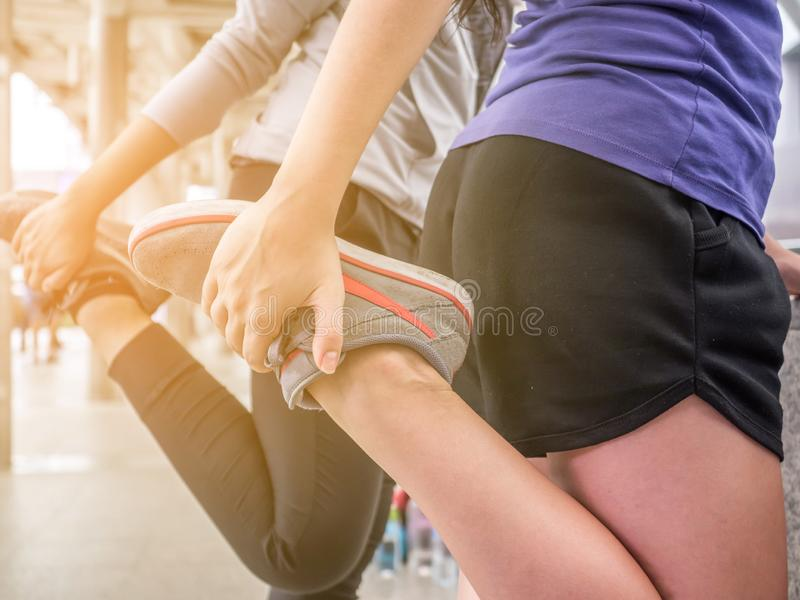 Female athlete lower body crop of feet doing legs stretches getting ready for cardio warmup. Running runner woman stretching leg stock image