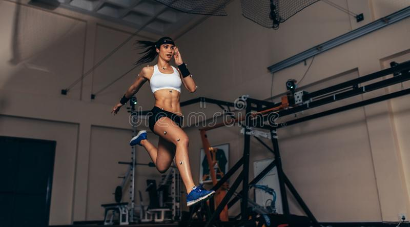 Movement and performance monitoring of runner in biomechanical l. Female athlete with motion capture sensors on her body running in biomechanical lab. Recording stock image