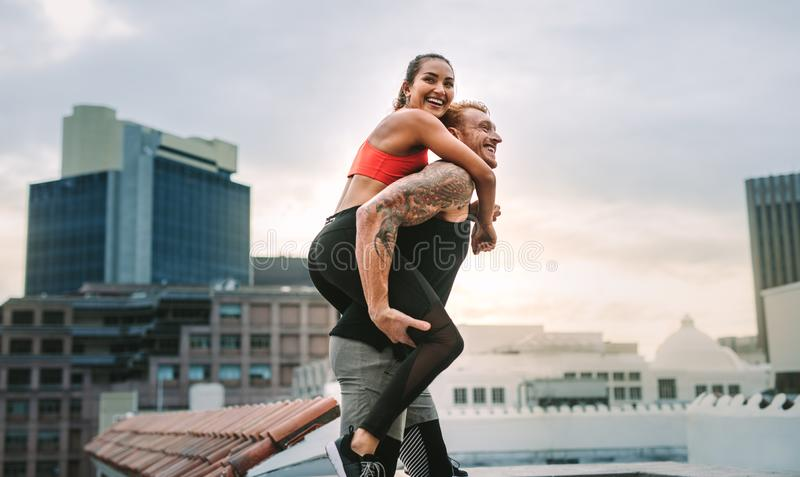 Female athlete piggy riding on a man while training on rooftop royalty free stock images