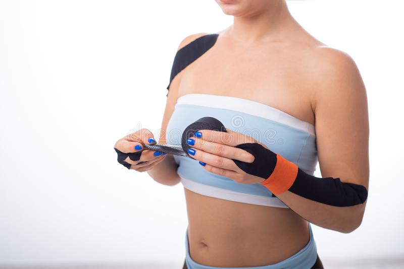 Female athlete puts a teip on her wrist. Kineziology, alternative treatment for injuries of joints and tendons. A woman is holding stock photos