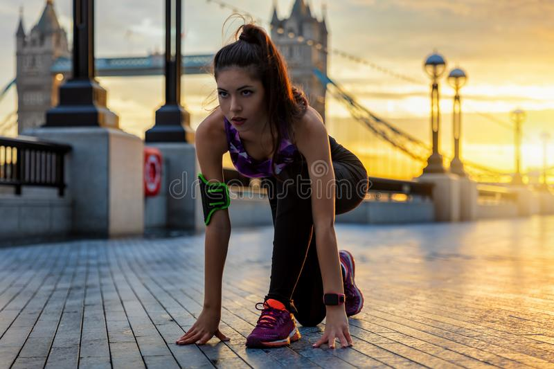 Female athlete ready to do her workout in an urban city. Pretty female athlete in starting position ready to do her workout during sunrise in an urban city stock photos