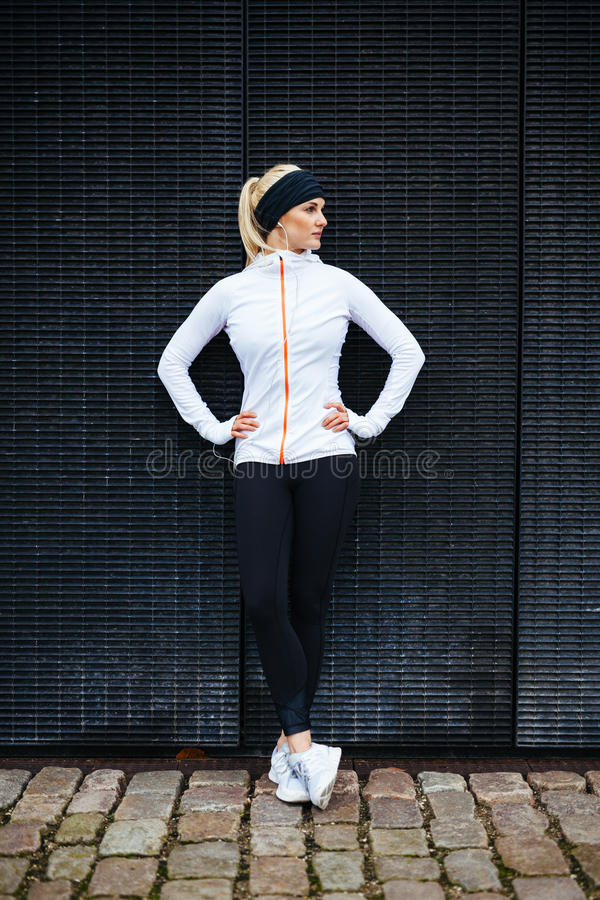 Female athlete resting after jogging in the city. Full length shot of sporty young woman relaxing after running exercise. Female athlete resting after jogging in stock photography