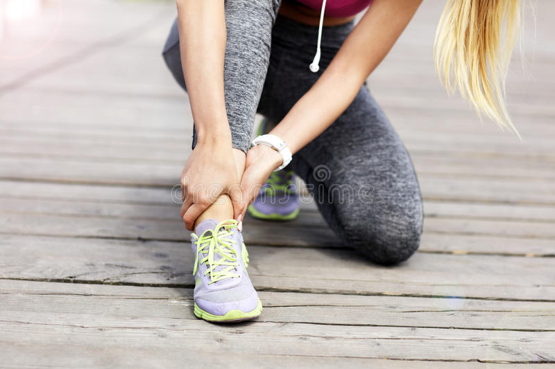 Female athlete runner touching foot in pain outdoors. Picture of female athlete runner touching foot in pain outdoors royalty free illustration