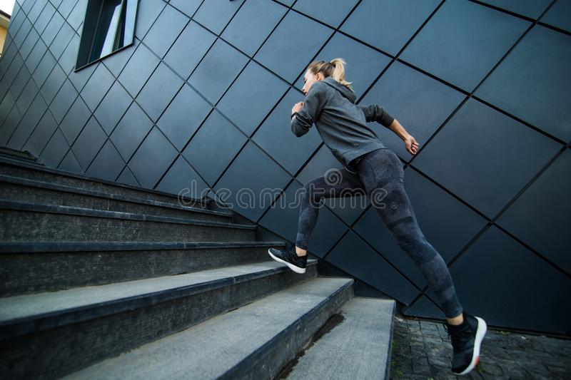 Female athlete running fast up the stairs staircase workout stock photo