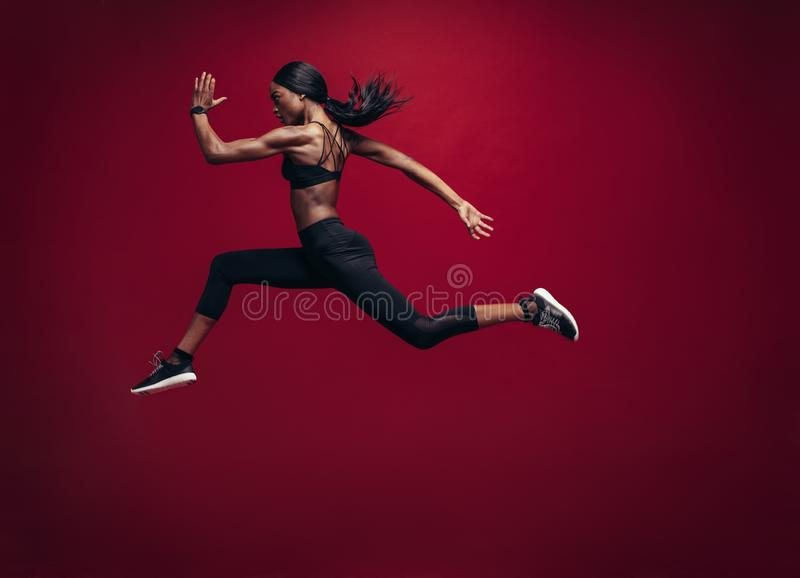 Female athlete running and jumping stock photo