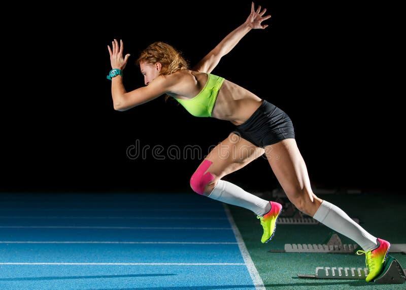 Female athlete starting her sprint race running. Female athlete starting sprint race running from blocks against black background royalty free stock image