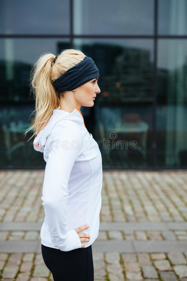 Female athlete on street preparing for a city run. Side view pf young sporty woman standing with her hands on hips outdoors. Caucasian female athlete on street stock images