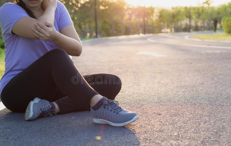 A female athlete suffering from arm and elbow pain and injury at the park. Sport and healthcare concept stock photos