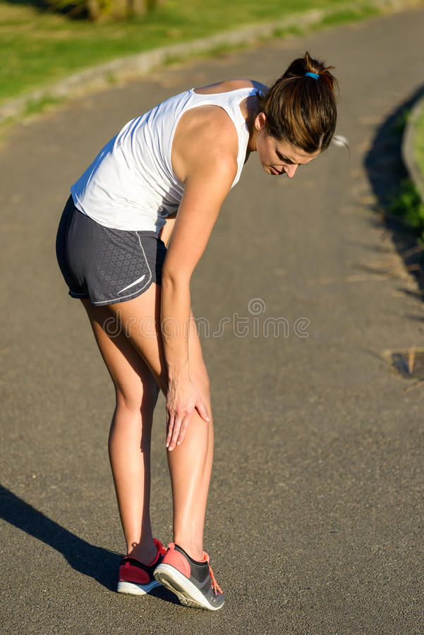 Female athlete suffering a calf muscle cramp injury while running. Female caucasian athlete suffering a calf muscle cramp injury while running outdoor in a park stock photography