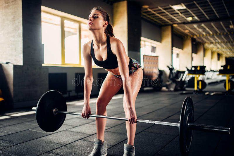 Female athlete training with barbell in sport gym stock image