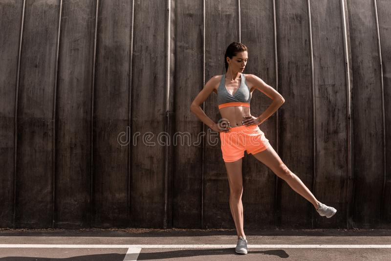 Female athlete training her legs. On parking stock image