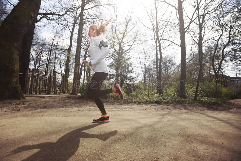 Female athlete training outdoor. Side view of caucasian female runner running outdoors in forest. Fitness woman athlete jogging in a park. Caucasian female model stock images