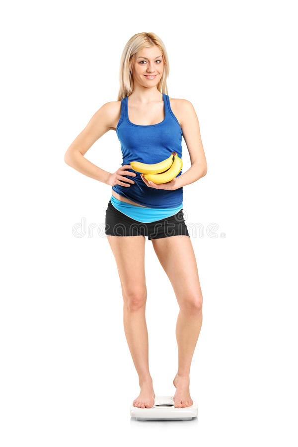 Female Athlete On A Weight Scale Holding Bananas Stock Images