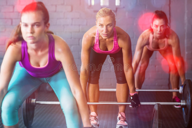 Female athletes lifting barbells. In gym stock image