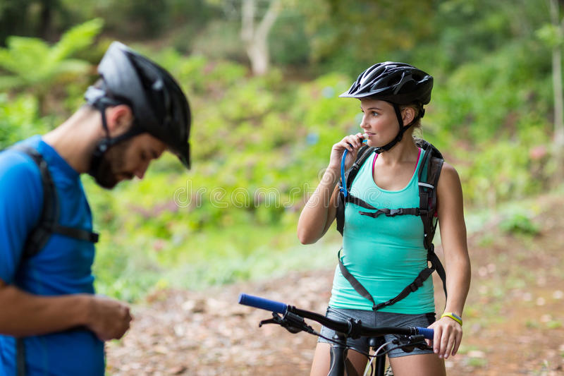 Female athletic drinking water from hydration pack. In forest stock photos