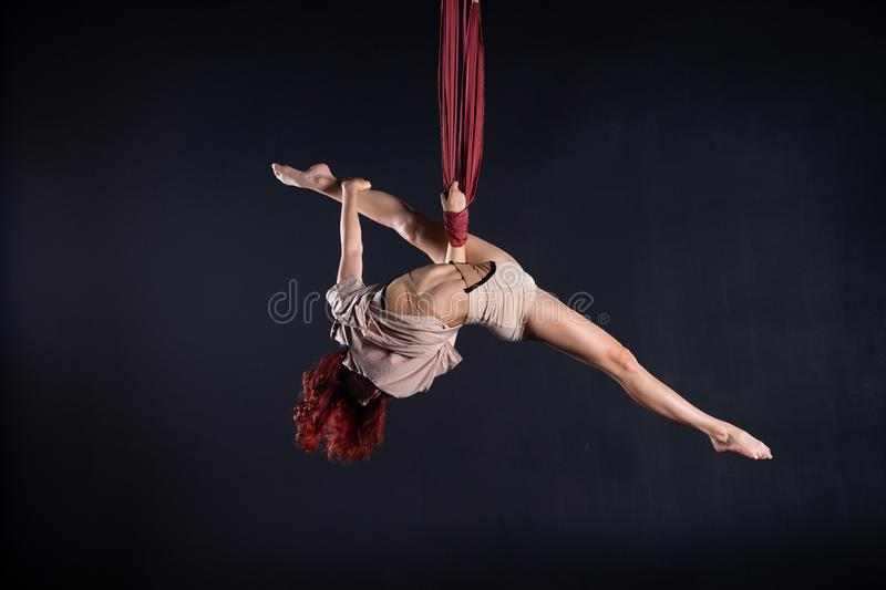 Female athletic, sexy and flexible aerial circus artist with redhead dancing in the air on the silk royalty free stock images