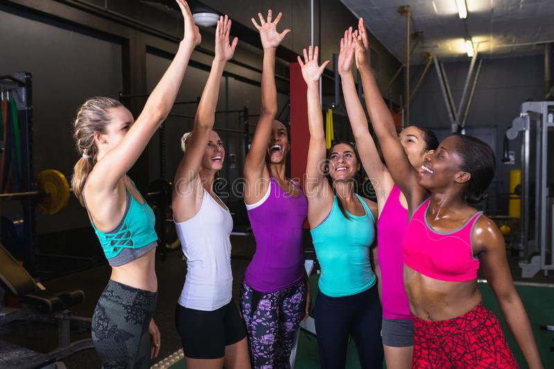Female athletic team giving high five to each other in fitness center royalty free stock images