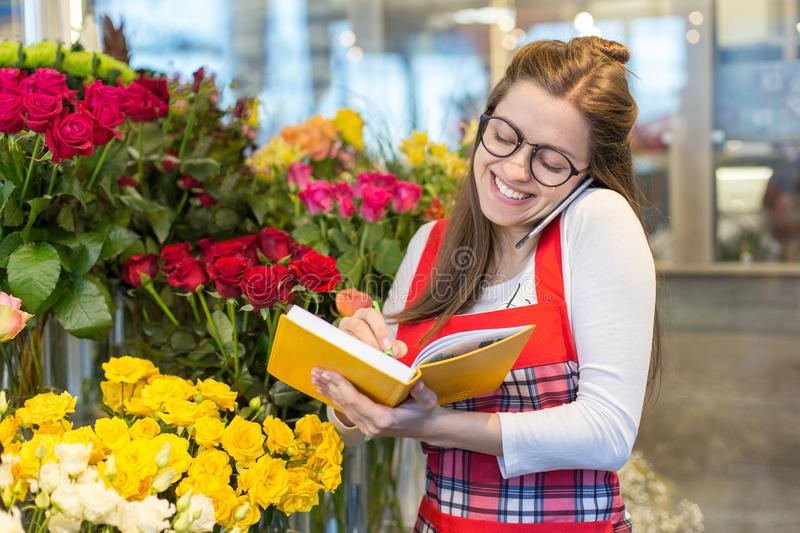Female attractive florist accepting orders over a phone and taking notes in a notebook in a flower shop. stock images