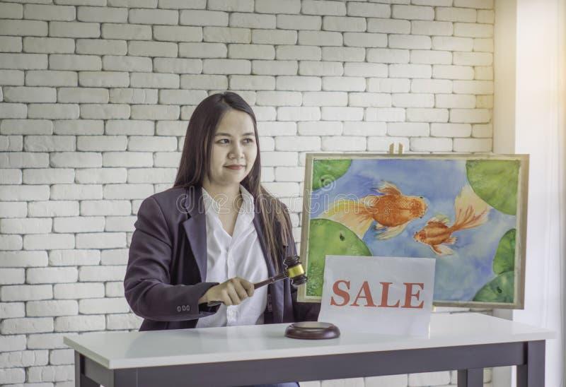 Female Auction Control, Hammer Knock to Goldfish Photo Auction, White Brick Background royalty free stock image