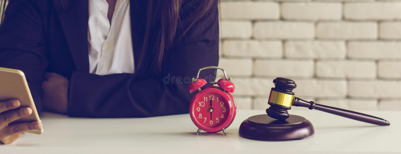 Female auctioneer controls,check list online auction winners,With retro alarm clock and golden brown wooden hammer placed on royalty free stock photo