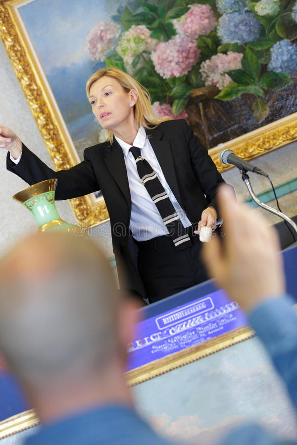 Female auctioneer directing bids royalty free stock photo