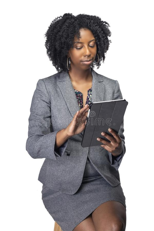 Female Author or Businesswoman Keynote Speaker with Tablet. Black African American teacher or businesswoman sitting and holding a tablet computer.  The confident stock photography