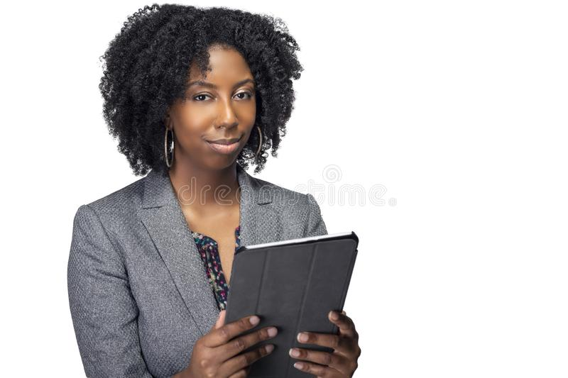 Female Author or Businesswoman Keynote Speaker with Tablet. Black African American teacher or businesswoman sitting and holding a tablet computer.  The confident royalty free stock photo