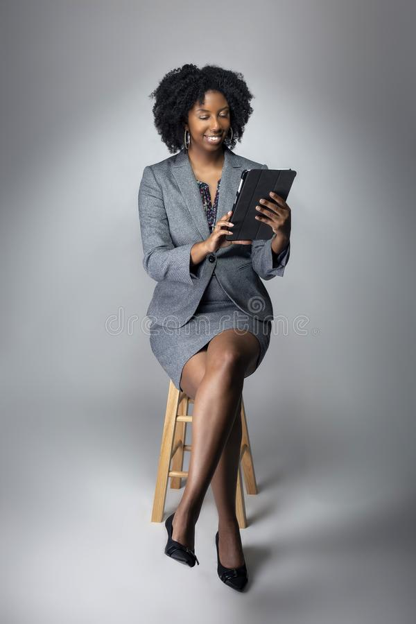 Female Author or Businesswoman Keynote Speaker with Tablet. Black African American teacher or businesswoman sitting and holding a tablet computer.  The confident stock images
