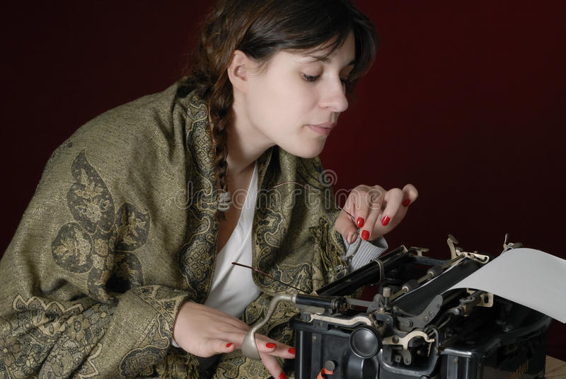 Female author typing on an old typewriter. Looking at what she already wrote on dark red background royalty free stock photos
