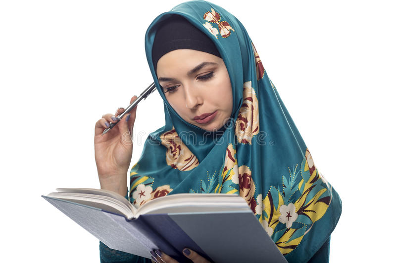 Female Author Wearing a Hijab. Female student author or journalist writing notes on a book with a pen. She is wearing a hijab associated with muslims or middle royalty free stock photography