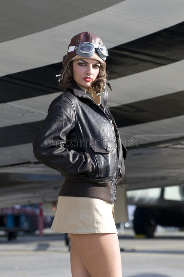 Female aviator. Attractive confident female aviator standing under an aircraft wing royalty free stock images