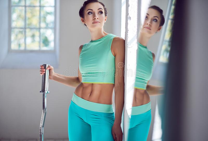 Female in azure sportswear holding berbell. royalty free stock photography