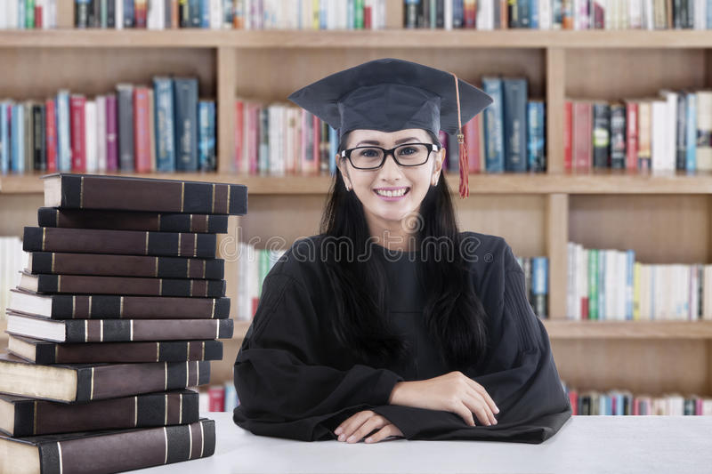Female bachelor and books in library stock photo