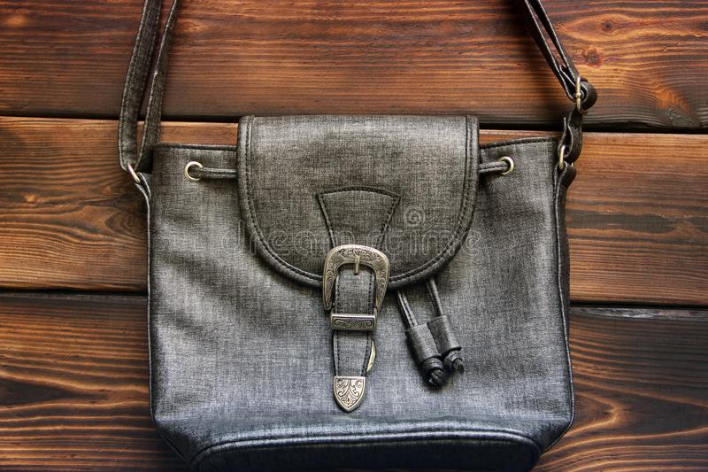 Female bag on a wooden background. Close up royalty free stock image