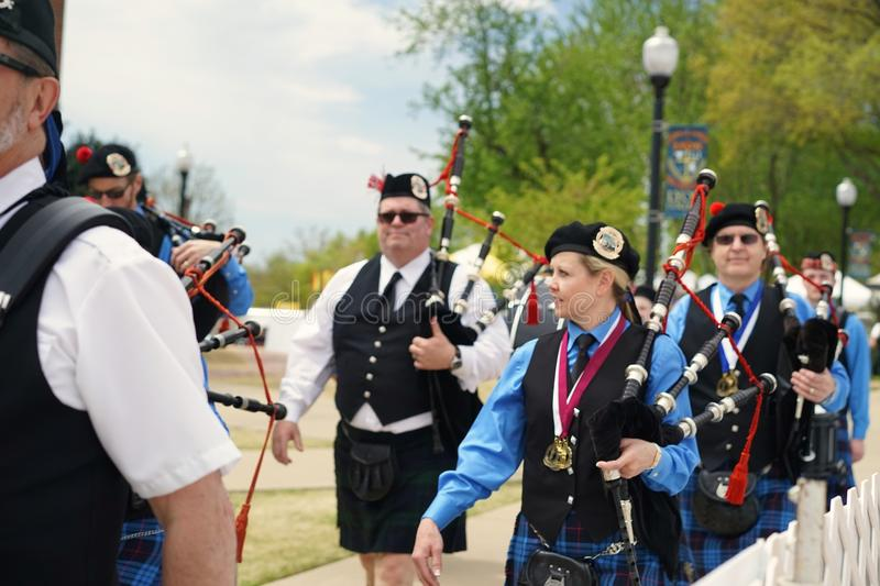 Female bagpiper in pipe and drum corps. Band marching in Scottish kilt and sporran after individual bagpipe competition at Lyon College Heritage Festival stock photo